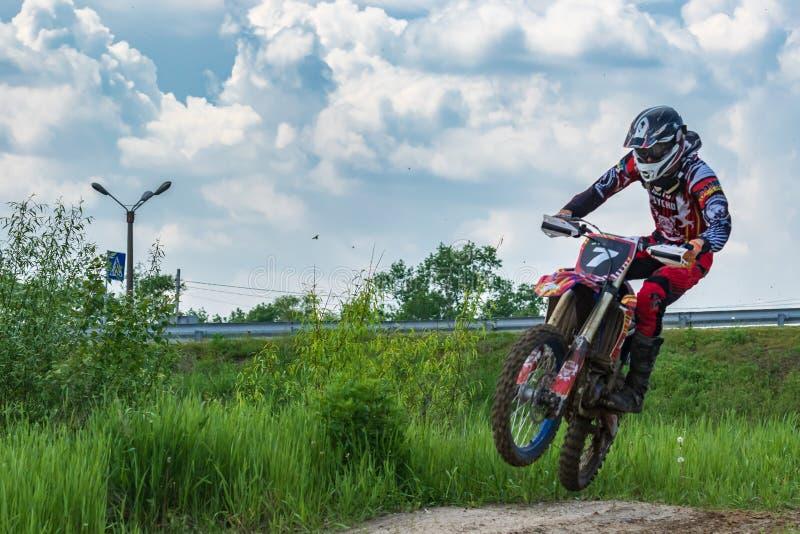 motocross Motorrijderstormlopen langs een landweg Groen in de voorgrond royalty-vrije stock fotografie