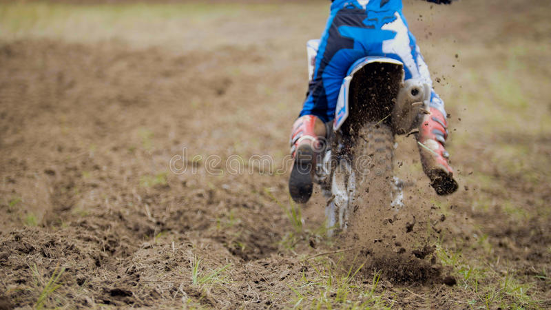 Motocross racer start riding his dirt Cross MX bike kicking up dust rear view, close up. Telephoto stock photos