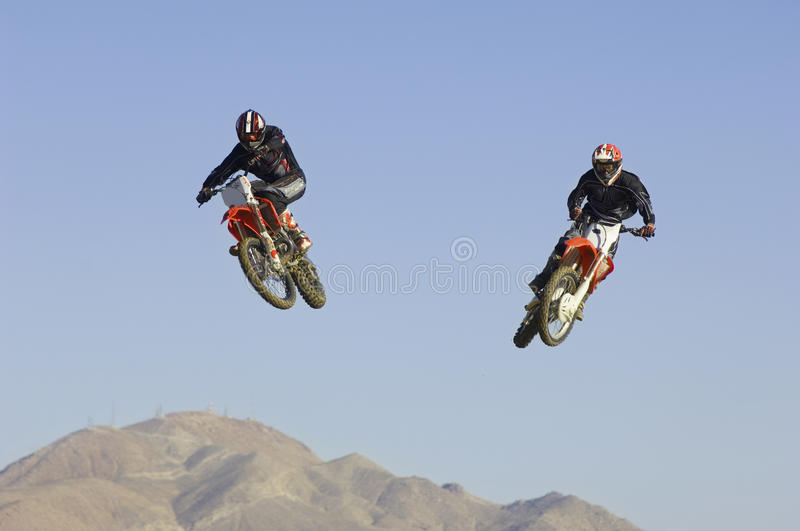 Motocross Racers Performing Stunt In Midair Against Blue Sky Royalty Free Stock Images
