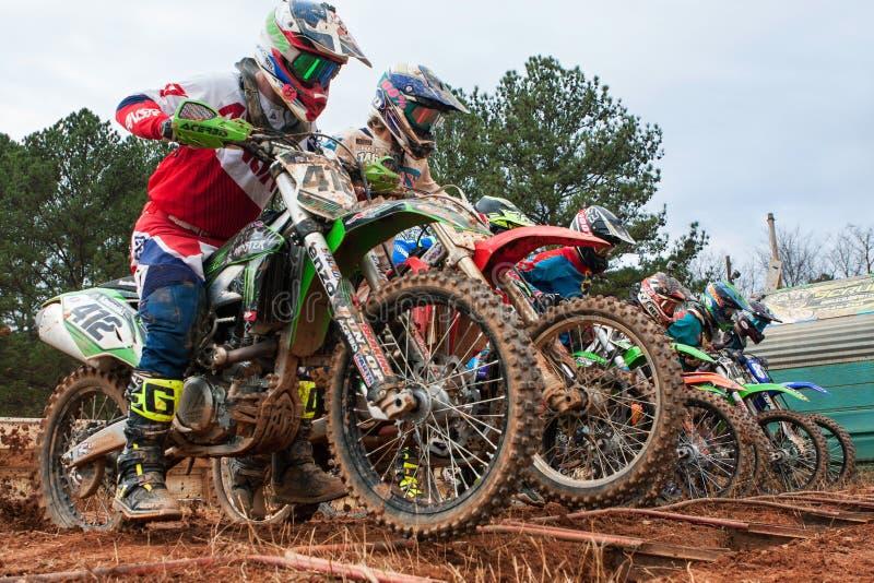 Motocross-Reiter stürzen vorwärts beim Anfang des Rennens los stockbilder