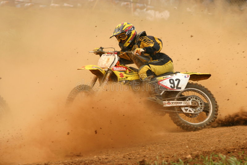 Motocross rider in curve with dust in the face stock photos