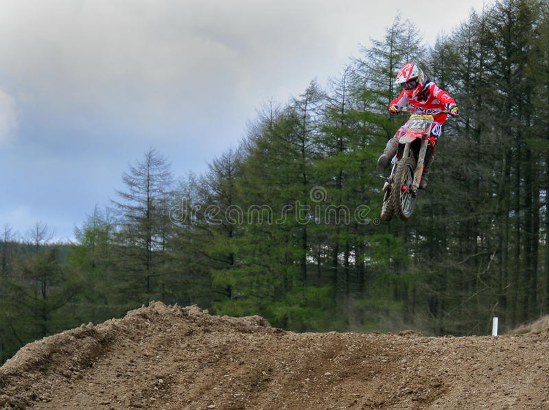Motocross rider jumping a rise stock photo