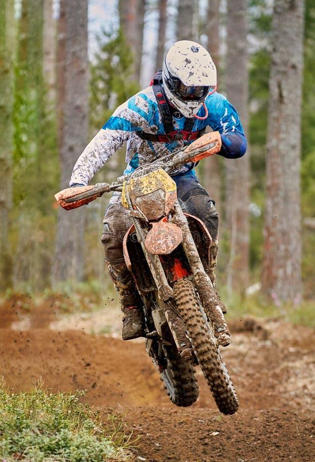 Motocrosschaufförbanhoppning med cykeln på den hög hastigheten på loppspåret royaltyfria bilder