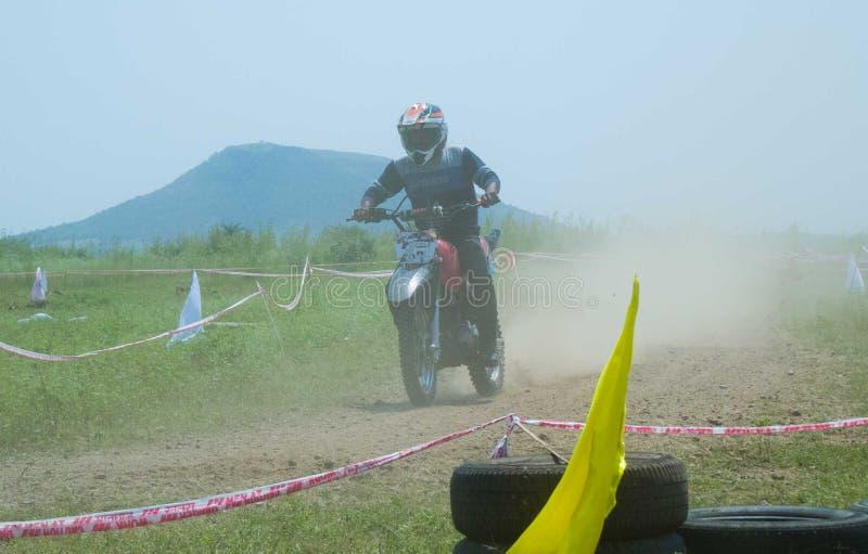 Motocrosscyklistryttare bak dammmolnet arkivbilder
