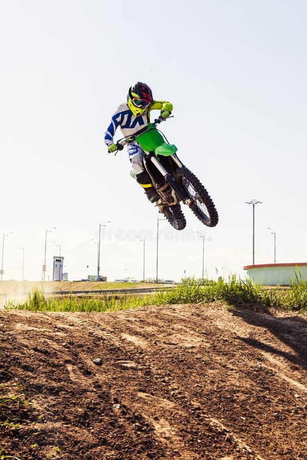Motocrossryttare i handling som accelererar mopeden royaltyfri fotografi