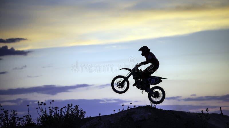 Motocrossryttarebanhoppning på solnedgången arkivfoton
