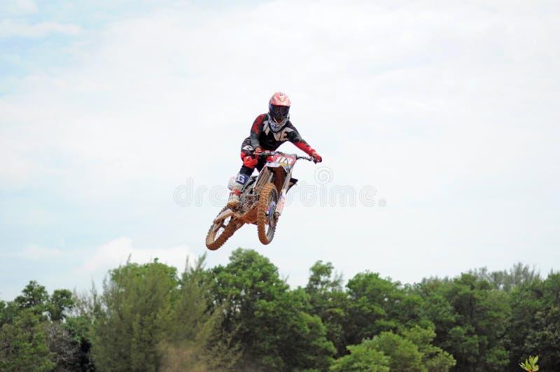 Motocrossryttaren gör en höjdhopputbildning på Kemaman, Terengganu, Malaysia motocrossspår fotografering för bildbyråer