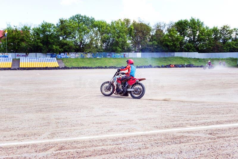 Motocrossryttaren skapar ett stort moln av damm och skr?p arkivbilder
