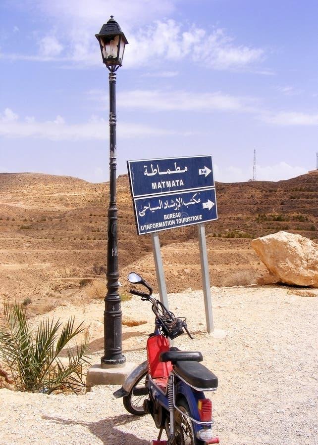 Motocycle, λαμπτήρας, οδικό σημάδι Matmata/γραφείο Indformation τουριστών στην έρημο στοκ φωτογραφία