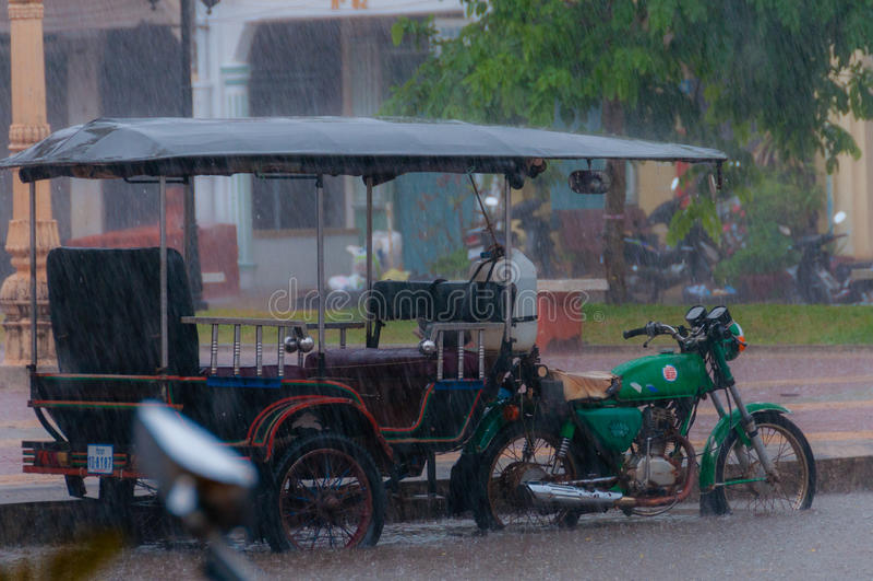 Motocycle de Tuktuk pendant la mousson de pluie dans Kampot image stock