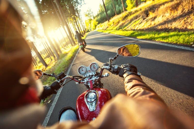 Motocyclette d'équitation de motocycliste dans le matin ensoleillé image stock