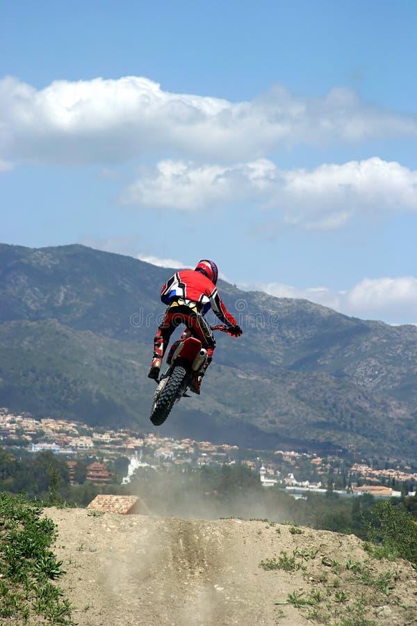 Motocyclette de Moto X branchant par l'air un jour ensoleillé chaud avec le grand ciel bleu photographie stock