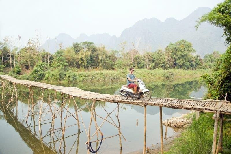 Motocyclette en bambou de pont de croisement de touristes gai, vue de chaux, Laos photographie stock