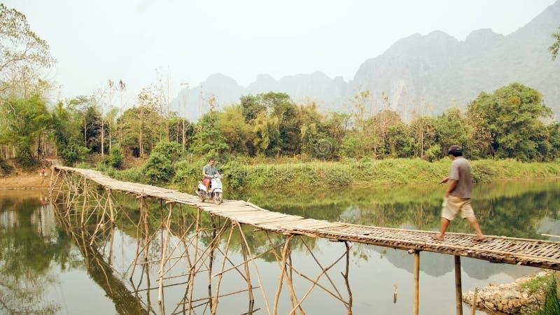Motocyclette en bambou de pont de croisement de touristes gai, vue de chaux, Laos images stock