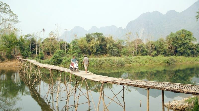 Motocyclette en bambou de pont de croisement de touristes gai, vue de chaux, Laos photos stock