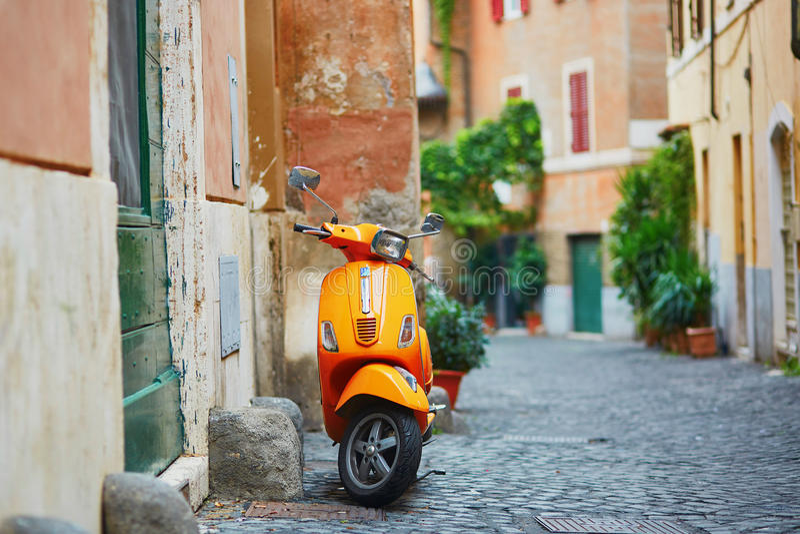 Motocyclette orange démodée sur une rue de secteur de Trastevere, Rome photo libre de droits