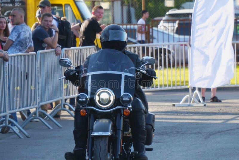 Motocycliste dans un casque montant une moto Harley Davidson images stock