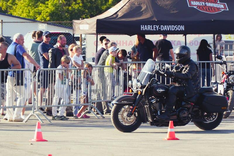 Motocycliste dans un casque montant une moto Harley Davidson photographie stock