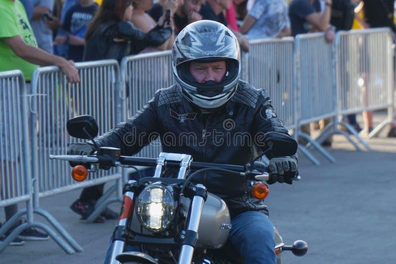 Motocycliste dans un casque montant une moto Harley Davidson photos stock