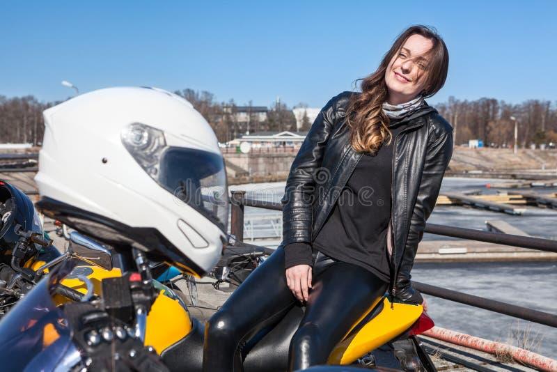Motocycliste heureux et souriant de jeune femme s'asseyant sur le dos de la moto, passager du cavalier, casque blanc sur un premi photo stock