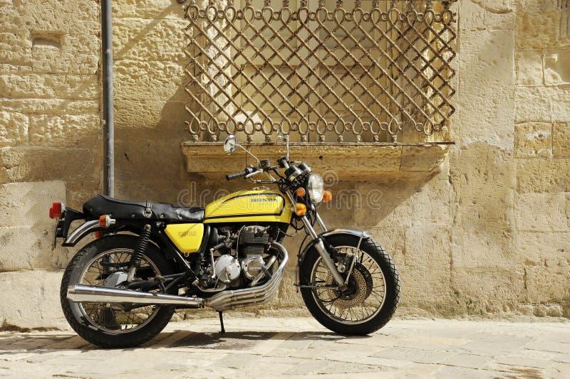 Motocykl Yellow Honda 400 stojący na ulicy starego włoskiego miasta Lecce, Apulia, Włochy obraz stock