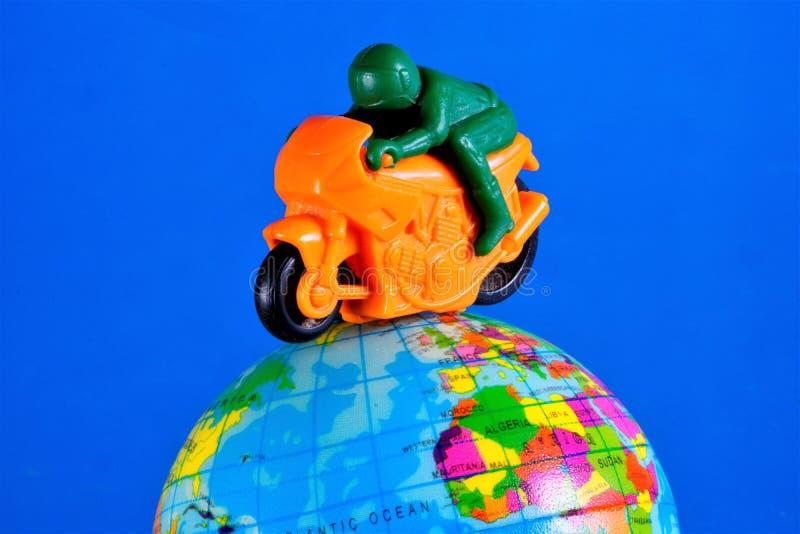 Motocykl zabawka z motocyklu setkarzem jedzie na kuli ziemskiej ziemia Motocykl jest dwukołowym pojazdem z machinalnym obraz royalty free
