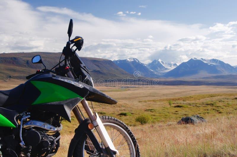 Motocyklu enduro podróżnik samotnie pod niebieskim niebem z białymi chmurami na tle halna dolina z śniegu lód zakrywającym szczyt obraz stock