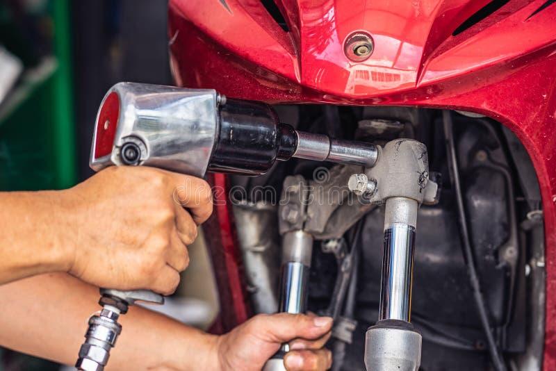 Motocyklu mechanik używa nasadkę na silniku a i wyrwanie zdjęcia royalty free