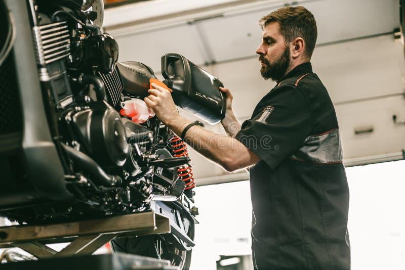 Motocyklu mechanik zamienia świeżego olej i nalewa w silnika zdjęcia royalty free