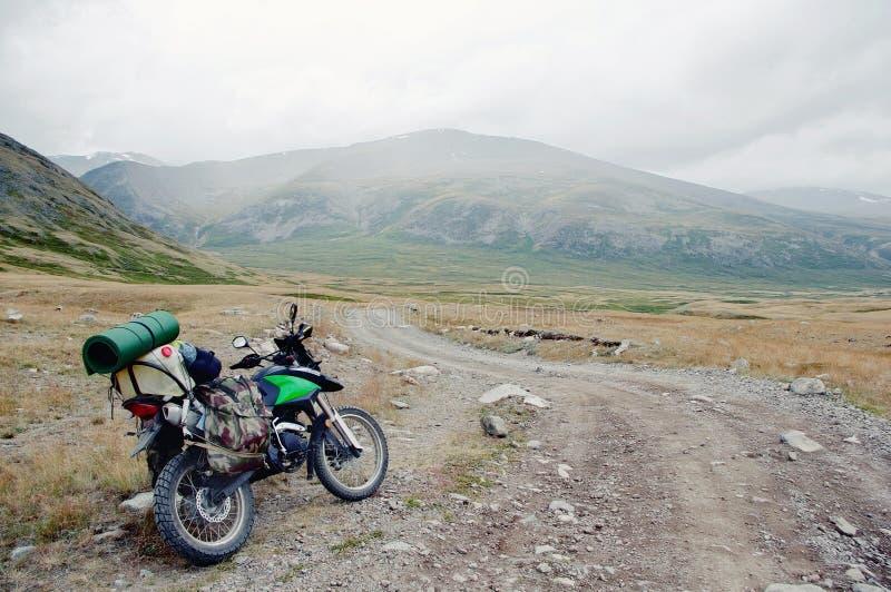 Motocyklu podróżnik stoi na krańcowej skalistej drodze w halnej dolinie w chmurnej pogodzie z walizkami fotografia stock