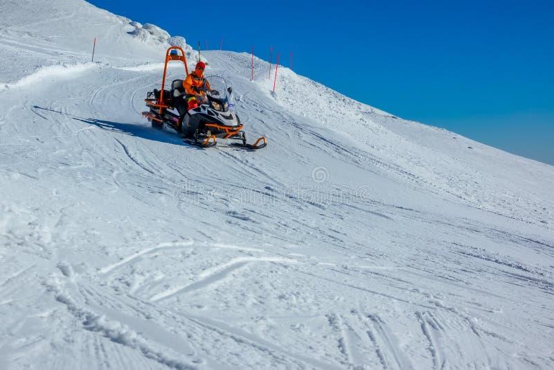 Motoneige de sauvetage en montagne sur une piste de ski images libres de droits