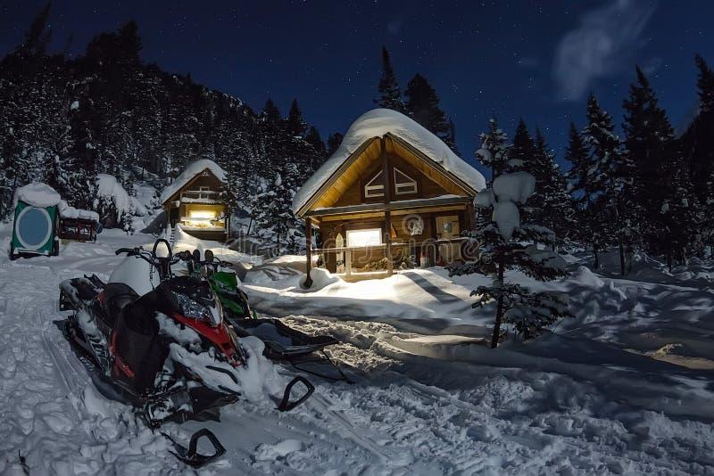 Motoneige des chalets de maison dans la forêt d'hiver avec la neige dans le ligh images stock