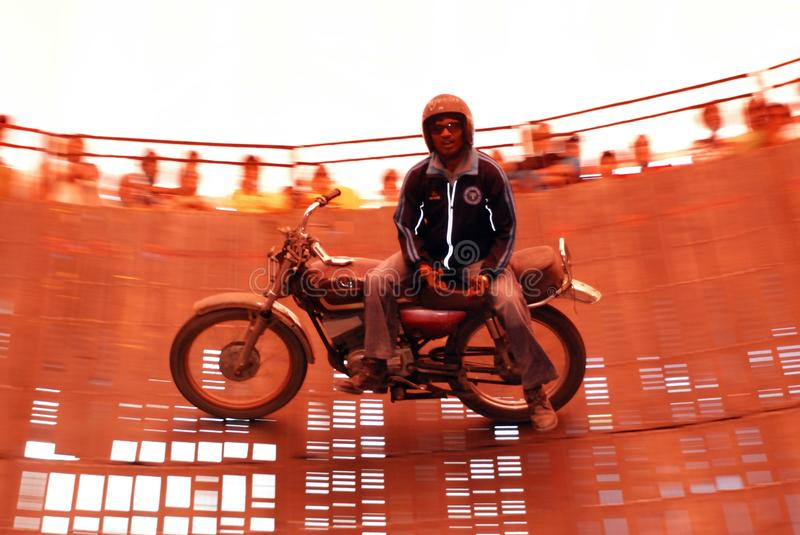 Motor bike rider on wall of death. Man riding a motorbike no handed on wall of death in India royalty free stock photos