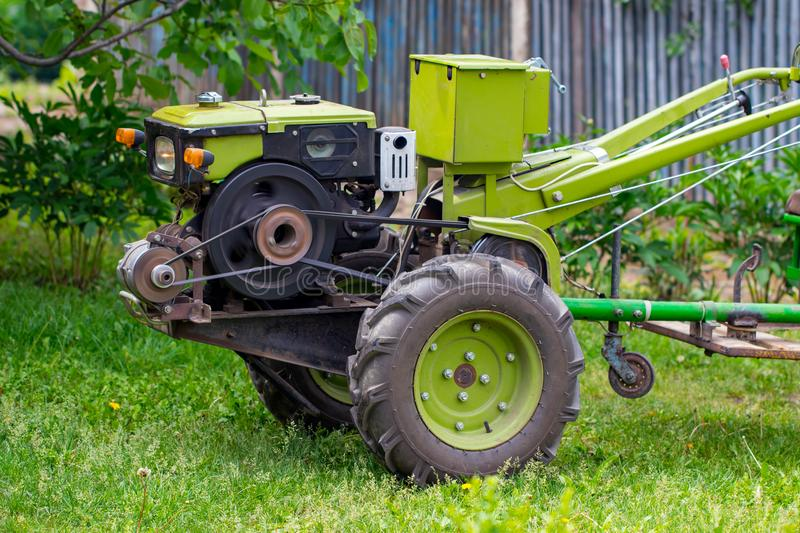Motor-block with green trailer. Development of traditional agricultural equipment and farming concept.  stock photos