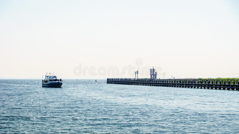 Motor boat entering the harbor of Urk in the Netherlands under a cloudless sky stock photo