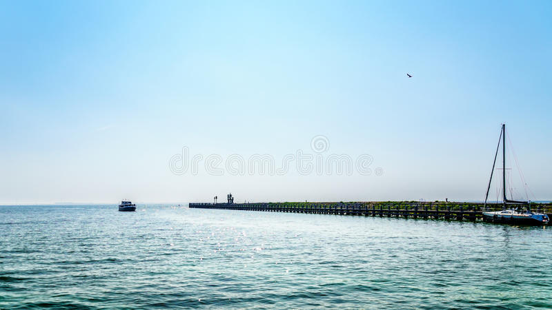Motor boat in the harbor of Urk in the Netherlands under a cloudless sky stock images