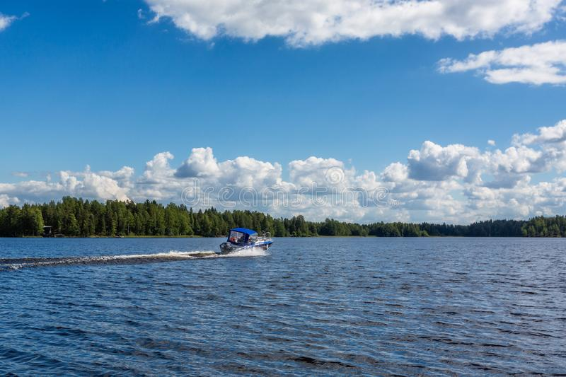 Motor boat moving on the big beautiful lake. Finland royalty free stock photography