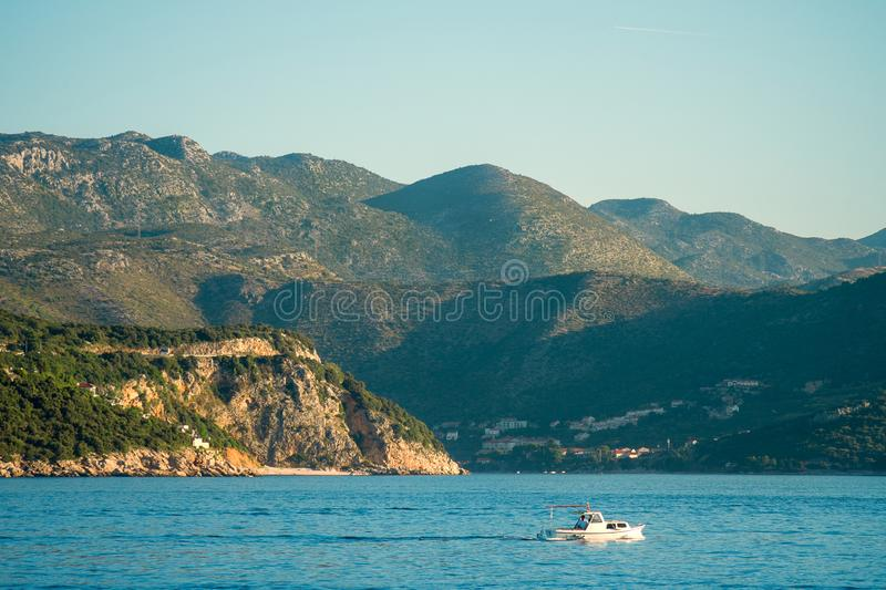 Motor boat is passing by a mountainous seashore with resort village in the valley. On a sunny day royalty free stock image
