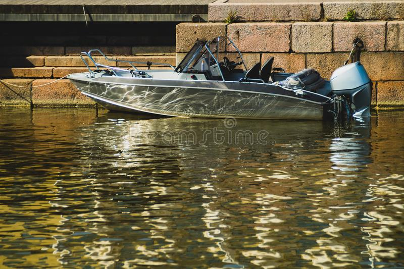 Motor boat on the pier. water transport in the dock. silver boat. reflection on the water. Motorboat on the pier. water transport in the dock. silver boat royalty free stock photo