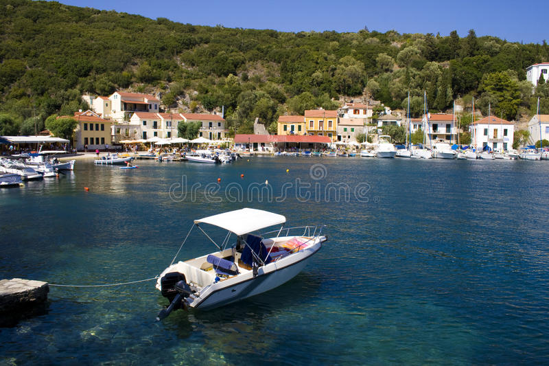 Motor boat in the port of Ithaca, Greece. Beautiful sea of Ithaca, homeland of Odysseus. The colorful houses in the background are reflected in the blue sea royalty free stock photos