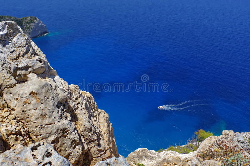 Motor boating on blue water - Zakynthos Island, landmark attraction in Greece. Ionian Sea. Seascape. White speedboat in the Ionian Sea, with white foam trail on stock photo