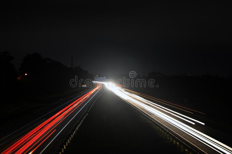 Motor car lights on highway at night stock photos