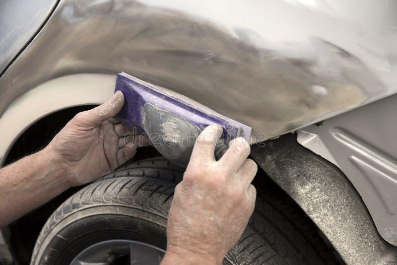 Motor car in repair shop. Close up of a mechanic sanding a panel on a car in panel repair shop stock photo