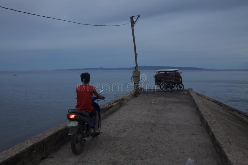 Motor-cyklist på pir på solnedgången fotografering för bildbyråer