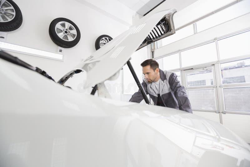 Motor de automóveis de exame masculino novo do mecânico de automóvel na oficina de reparações foto de stock