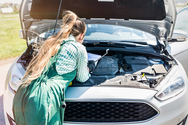 Motor de automóveis de exame do mecânico da mulher com prancheta fotografia de stock
