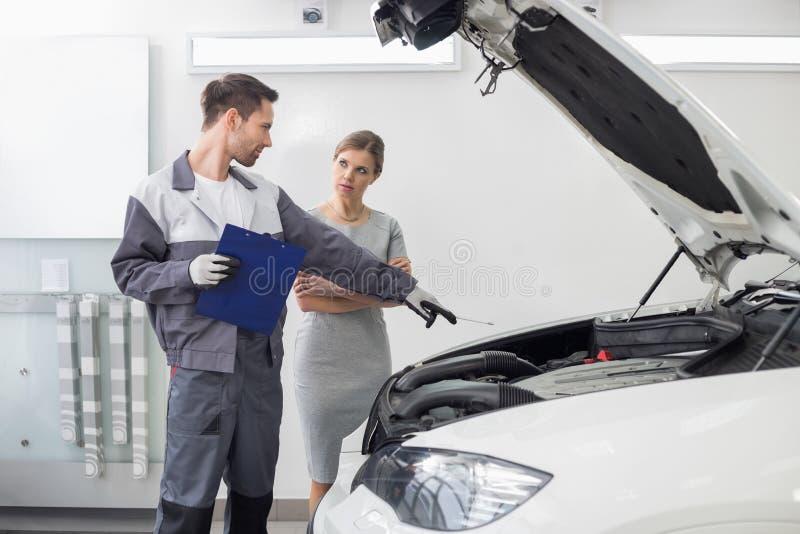 Motor de coche de explicación del reparador de sexo masculino joven al cliente femenino en el taller de reparaciones del automóvi imagen de archivo libre de regalías