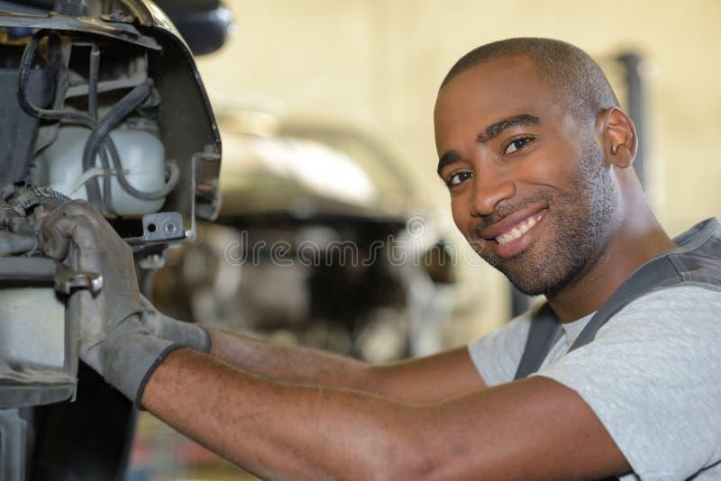 Motor de coche sonriente de la fijación del mecánico en garaje imagen de archivo libre de regalías