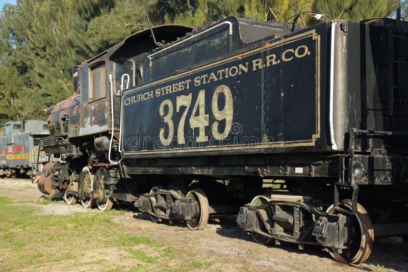 Motor do trem do vintage com o carro de carvão da estrada de trilho da estação da rua da igreja fotografia de stock royalty free