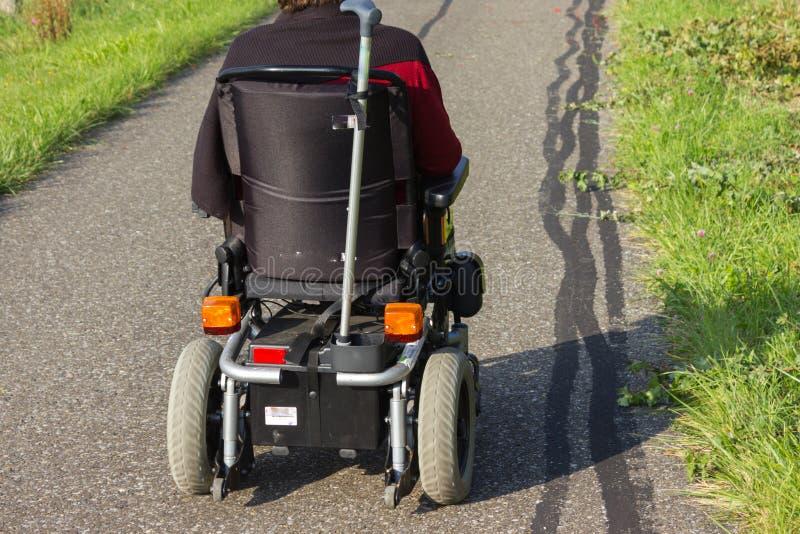 motor-drivande hjulstol på en gata i den september nedgången royaltyfri bild